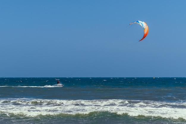 Kiteboardingsurfer die in het overzees vliegt