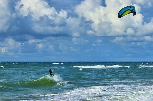 Kitesurfer op de top van een golf. blauwe lucht met witte wolken en turquoise zee