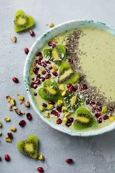 Kiwi-banaan smoothies kom met havermout, pistachenoten, granaatappelpitjes en chia op lichtgrijze stenen achtergrond