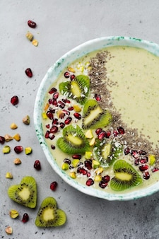 Kiwi-banaan smoothies kom met havermout, pistachenoten, granaatappelpitjes en chia op lichtgrijze stenen ondergrond. selectieve aandacht. bovenaanzicht.