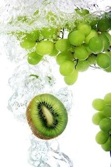 Kiwi en druif vallen in water