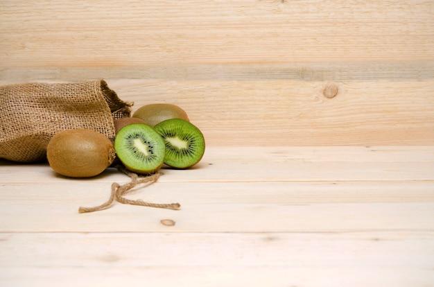 Kiwi en een zak jute op een houten achtergrond en kopieer ruimte