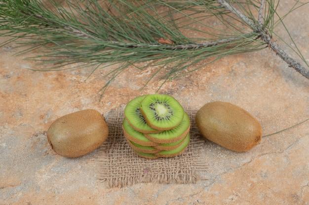 Kiwi en kiwi plakjes op marmeren oppervlak.