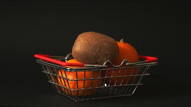 Kiwi en sinaasappel zitten in een kleine supermarktmand