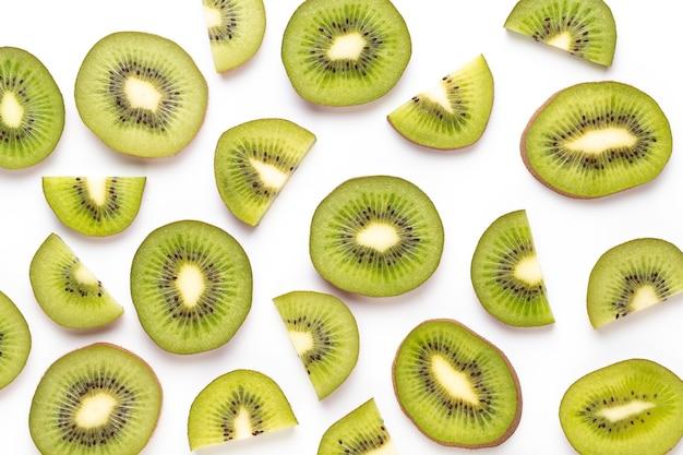 Kiwi fruit plakjes macro. rijp kiwifruit dat op witte achtergrond wordt geïsoleerd. plat leggen.