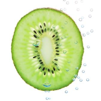 Kiwi in een vloeistof met bubbels. op een witte muur.