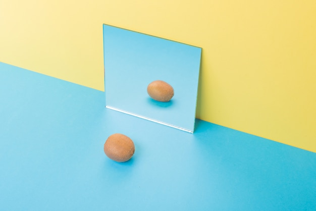 Kiwi op blauwe tafel geïsoleerd op geel in de buurt van spiegel