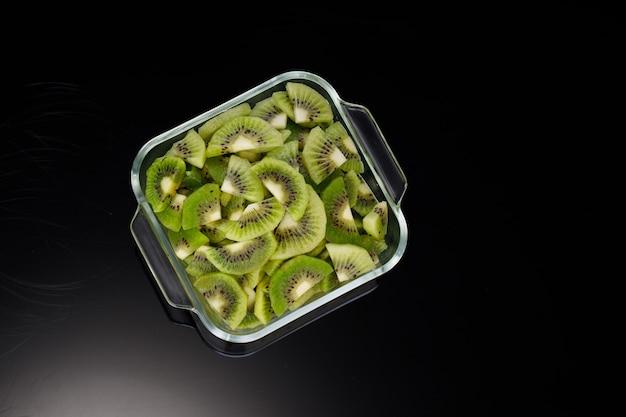 Kiwi plakjes of gesneden stuk gerangschikt in een glazen vierkante container met zwarte kleur achtergrond.