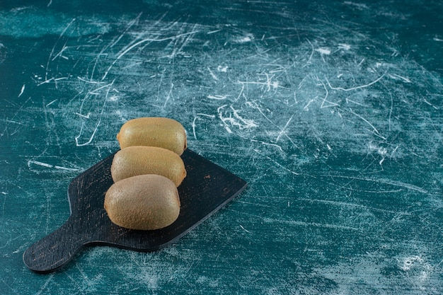 Kiwi's op snijplank, op de marmeren tafel.