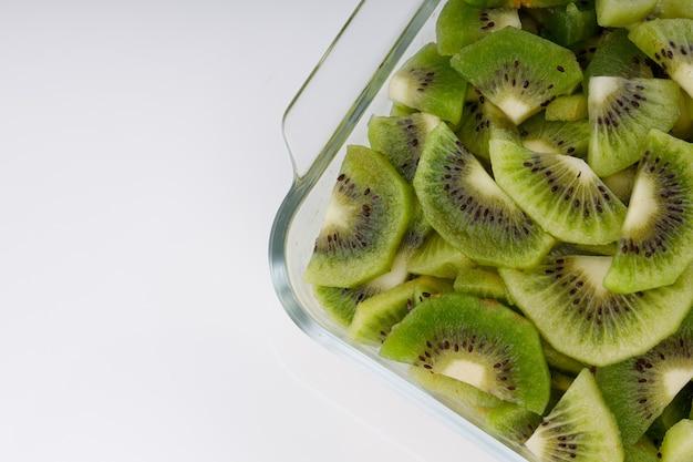 Kiwi's plakjes of gesneden stuk gerangschikt in een glazen vierkante container met witte kleur achtergrond.