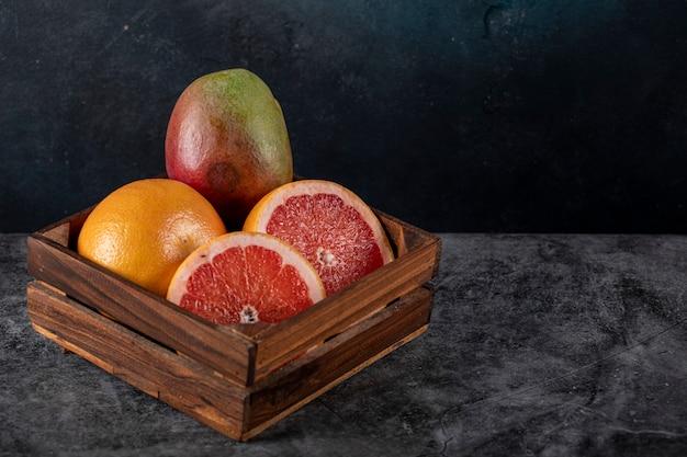 Kiwi, sinaasappel en grapefruit segmenten in een houten bakje op een donkere marmer