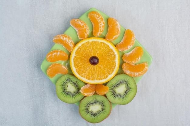 Kiwi, sinaasappel en mandarijn plakjes op groene plaat. hoge kwaliteit foto