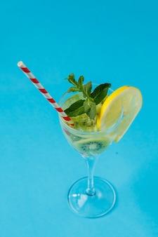 Kiwicocktail gegarneerd met citroen en munt in een glas op een servet tegen een blauwe ondergrond