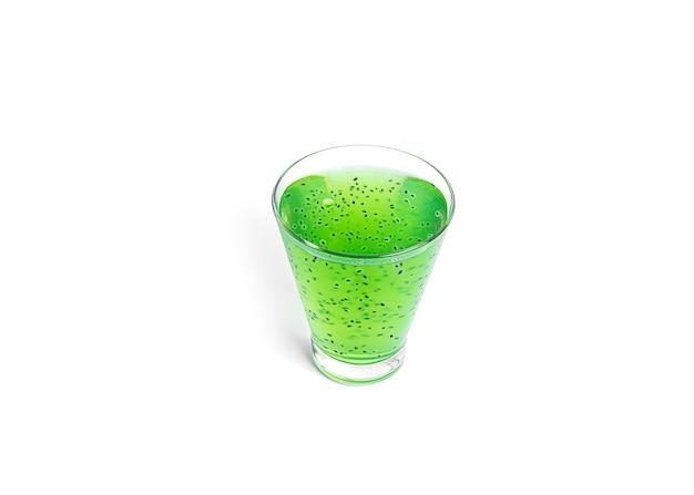 Kiwidrank met geïsoleerde basilicumzaden. groene kiwi-smoothie.