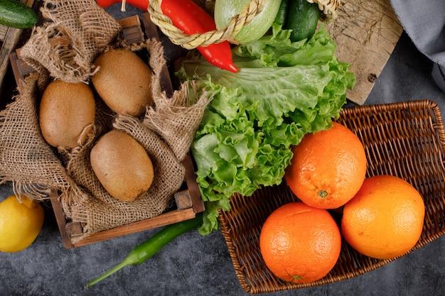 Kiwies en sinaasappels in rustieke houten bakjes.