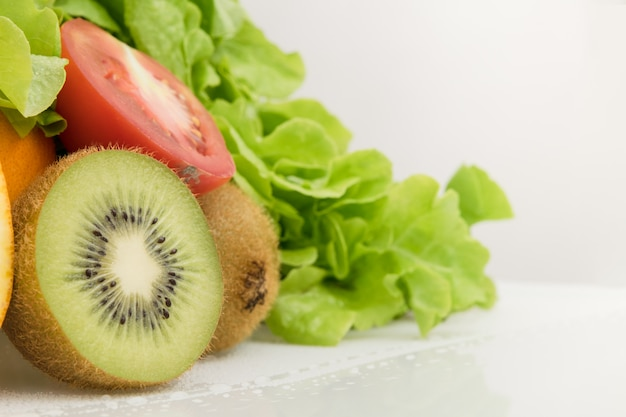Kiwifruit en groente op wit. tomaat en sla. gezond voedsel.