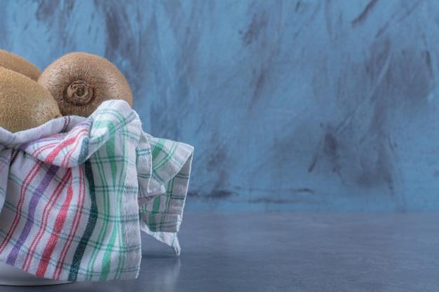 Kiwivruchten op handdoek in kom op marmeren tafel.