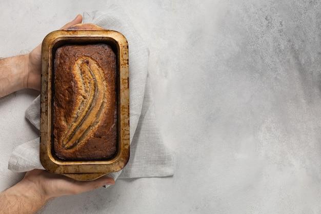 Klaar bananenbrood in een rechthoekige ovenschaal in de mannelijke handen van de bakker op een lichte achtergrond
