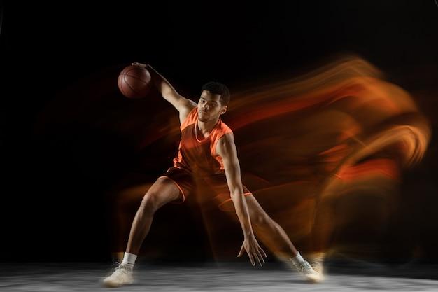 Klaar. jonge arabische gespierde basketbalspeler in actie, beweging geïsoleerd op zwart in gemengd licht