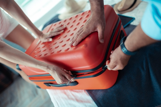 Klaar maken. handen van twee mensen die op een zijkant van een koffer duwen en proberen deze te sluiten en dicht te ritsen.