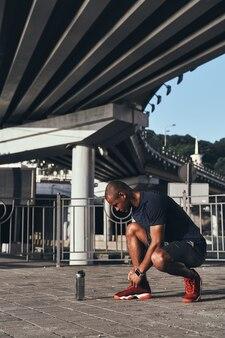Klaar maken. knappe jonge afrikaanse man in sportkleding die schoenen bindt terwijl hij buiten staat