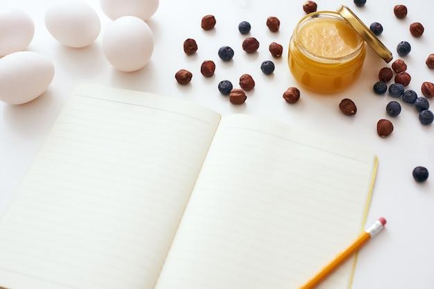 Klaar om een recept te schrijven. potlood en kookboek liggen op tafel bij gedroogde bessen, honing en eieren