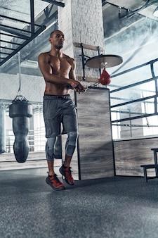 Klaar om elk obstakel te overwinnen. volledige lengte van jonge afrikaanse man in sportkleding springtouw