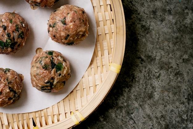 Klaar om gehaktballen op papier te koken boven een aziatisch bamboe dienblad. bovenaanzicht. plat leggen.