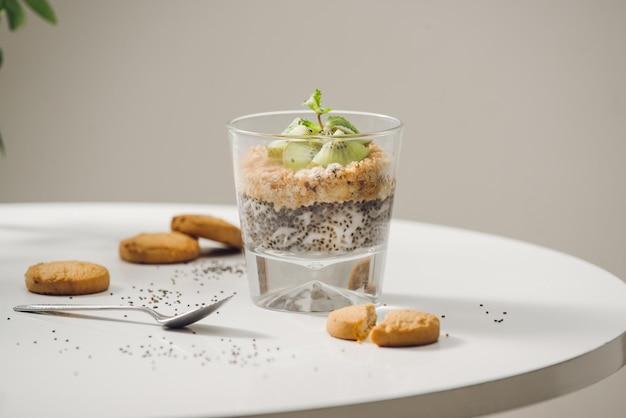 Klaar om gezond een voedzaam ontbijt te eten - granola met amandelen, chiazaden, banaan en kiwivruchten en bessen en een kruik met melk in de buurt