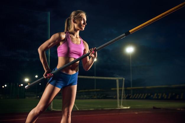 Klaar om moeilijkheden te overwinnen. professionele vrouwelijke polsstokhoogspringer training in het stadion in de avond. buiten oefenen. begrip sport