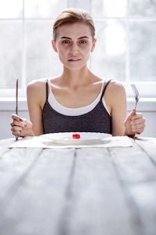 Klaar om te eten. leuke bleke vrouw die een vork en een mes vasthoudt terwijl ze klaar is om te eten