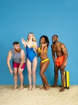 Klaar om te feesten. gelukkige jonge vrienden die en pret op blauwe studioachtergrond rusten. concept van menselijke emoties, gezichtsuitdrukking, zomervakantie of weekend. chill, zomer, zee, oceaan.