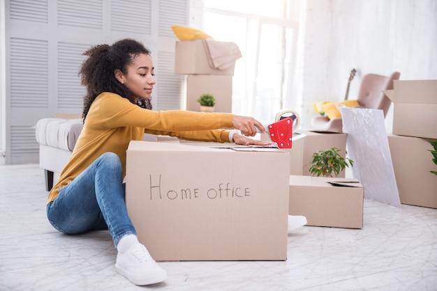 Klaar om te gaan. charmant jong meisje, zittend op de vloer en het sluiten van een doos met dingen voor een kantoor aan huis met plakband