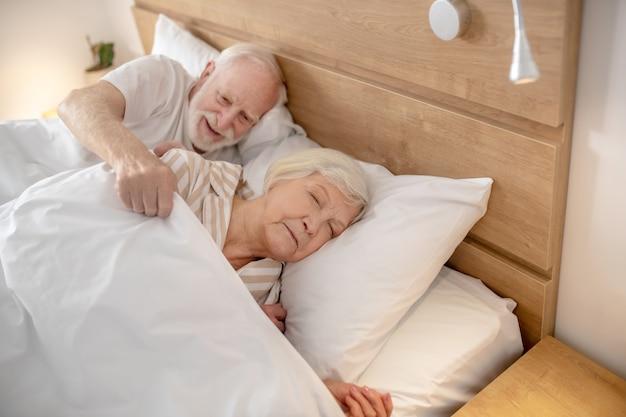 Klaar om te gaan slapen. bejaarde die zijn vrouw bedekt met de deken