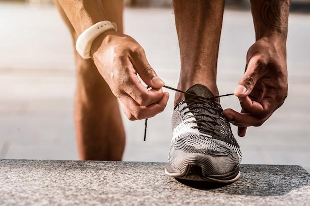 Klaar om te gaan. sluit omhoog van mannelijke sportschoenen die door een jonge professionele atleet worden geregen