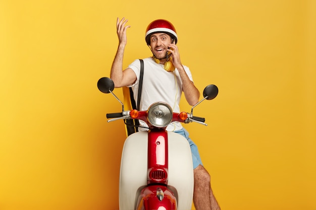Klaar om te rijden. gelukkig verward mannelijke rijder zit op scooter, heeft telefoongesprek terwijl stopt op de weg, arm omhoog houdt, kleine rugzak draagt, beschermende helm draagt, werkt in de bezorgdienst