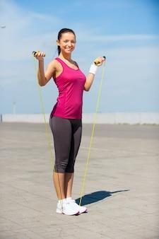 Klaar om te springen. volledige lengte van mooie jonge vrouw in sportkleding die touwtjespringt vasthoudt en glimlacht terwijl ze buiten staat