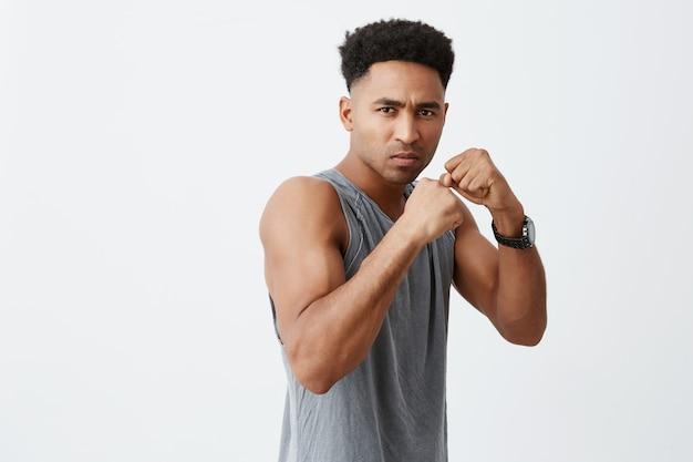 Klaar om te vechten. sport, schoonheid en gezonde levensstijl concept. sluit omhoog van jonge aantrekkelijke donkerhuidige afro mannelijke bokser die met krullend haar in camera kijken, geconcentreerd zijn, gaand winnen.