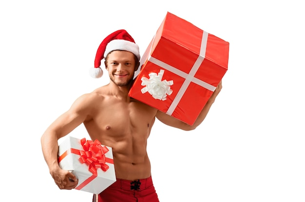 Klaar om te vieren. sexy aantrekkelijke man met een kerstmuts die lacht en cadeautjes vasthoudt die zijn gescheurde lichaam laten zien