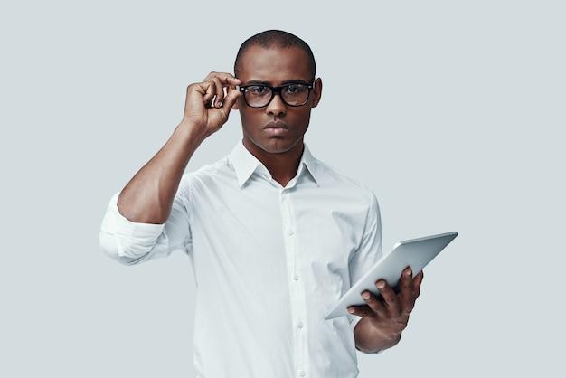 Klaar om te werken. knappe jonge afrikaanse man die digitale tablet gebruikt en naar de camera kijkt terwijl hij tegen een grijze achtergrond staat