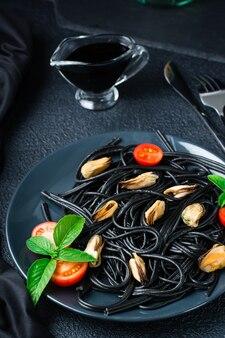 Klaar om zwarte spaghetti te eten met mosselen, tomaten en basilicum op een bord en sojasaus op een zwarte achtergrond. foodfotografie in donkere kleuren. detailopname. verticale weergave