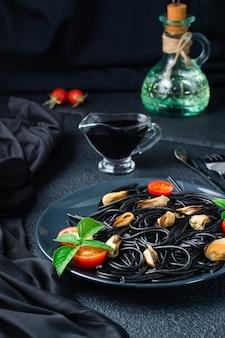 Klaar om zwarte spaghetti te eten met mosselen, tomaten en basilicum op een bord en sojasaus op een zwarte achtergrond. foodfotografie in donkere kleuren. verticale weergave