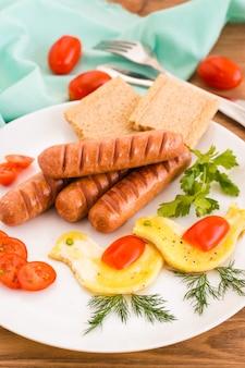 Klaar ontbijt. gebakken worstjes, roerei, tomaten en greens.