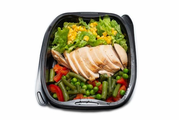 Klaar voedsel in een container. gestoofde kip, gestoofde groenten. geïsoleerd op een wit oppervlak