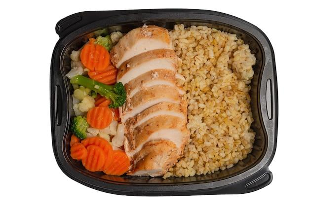 Klaar voedsel in een container. gestoofde kip, gestoofde wortel, kool en pap. geïsoleerd op wit.