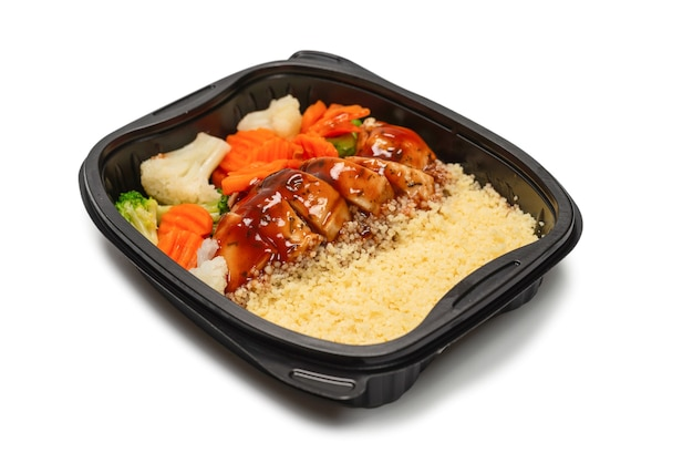 Klaar voedsel in een container. gestoofde kip in teriyakisaus, gestoofde wortel, kool en pap. geïsoleerd op een wit oppervlak
