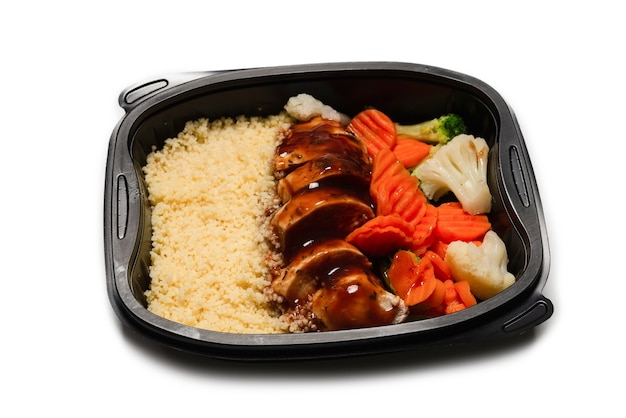 Klaar voedsel in een container. gestoofde kip in teriyakisaus, gestoofde wortel, kool en pap. geïsoleerd op een wit oppervlak.