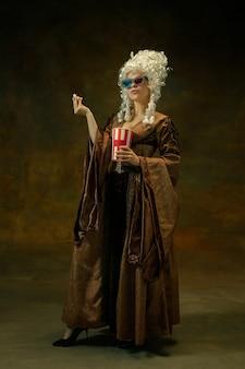 Klaar voor de bioscoop. portret van middeleeuwse vrouw in vintage kleding met 3d-brillen, popcorn op donkere achtergrond. vrouwelijk model als hertogin, koninklijk persoon. concept vergelijking van tijdperken, mode, schoonheid.