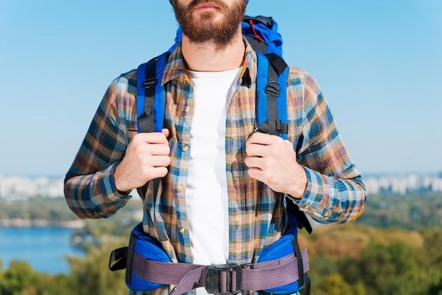Klaar voor de nieuwe openingen. close-up van een jonge man die een rugzak draagt terwijl hij tegen een stedelijk landschap staat
