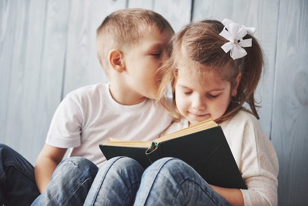 Klaar voor grote reizen. gelukkig meisje en jongenslezing intereting boek die een grote aktentas en het glimlachen dragen. reizen, vrijheid en verbeelding